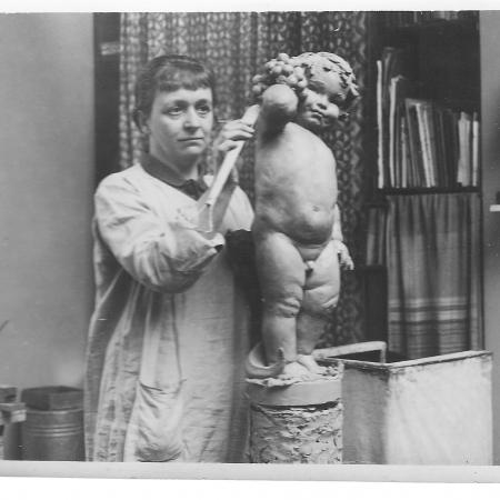Anne Acheson putting her finishing touches to a sculpture called October in the 1920s